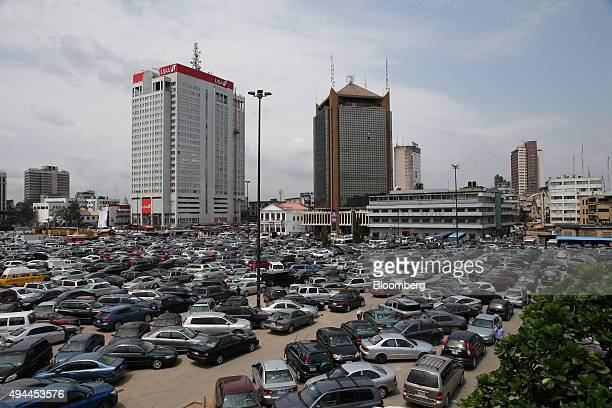 The offices of United Bank for Africa Ltd left and Wema Bank Plc center stand beyond a crowded parking lot in the business district of Lagos Nigeria...