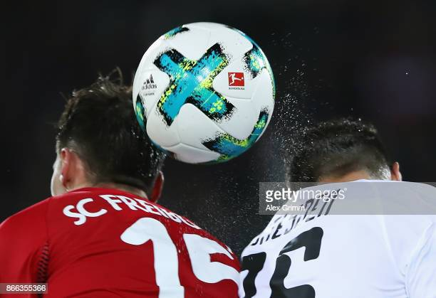 The official adidas matchball Torfabrik is seen as Pascal Stenzel of Freiburg jumps for a header with Philip Heise of Dresden during the DFB Cup...