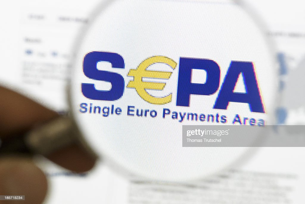 The official Logo of Single Euro Payments Area ( SEPA ) is seen on a computer screen through a magnifying glass on October 24, 2013 in Berlin, Germany. SEPA is an initiative of the European banking industry that will make all electronic payments across the euro area and the deadline for euro area countries to migrate to the SEPA credit transfer and direct debit schemes is set at February 1, 2014. The second migration progress report released today by The European Central Bank (ECB) warned against late migration to the new schemes.
