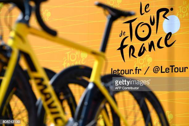 The official logo of the Tour de France is pictured behind bikes prior to the 2075 km fourth stage of the 104th edition of the Tour de France cycling...
