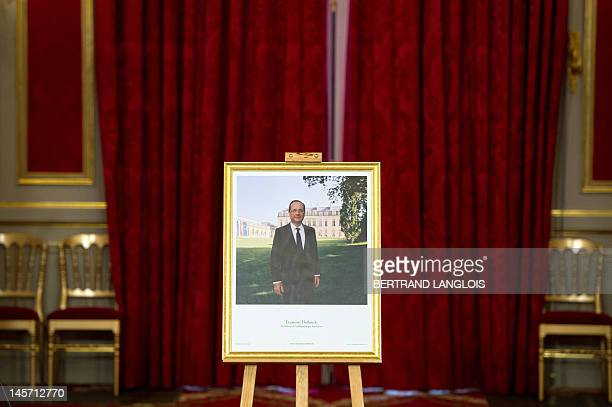 The official portrait of French President Francois Hollande made by French photographer Raymond Depardon stands in the ball room of the Elysee...