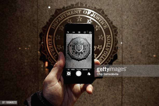 The official seal of the Federal Bureau of Investigation is seen on an iPhone's camera screen outside the J Edgar Hoover headquarters February 23...