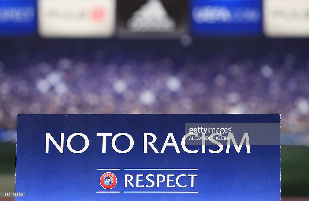 The official UEFA Champions League 'No to Racism' campaign logo is seen during a press conference of Austrian football club Austria Wien ahead of a training session in Vienna on October 21, 2013 on the eve of their group stage UEFA Champions League football match between Austria Vienna and Atletico de Madrid. AFP PHOTO / ALEXANDER KLEIN