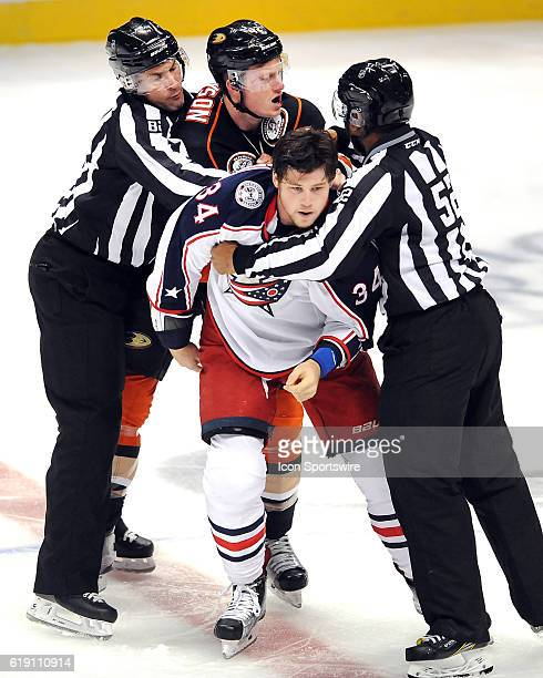 The officials break up a fight between Anaheim Ducks defenseman Josh Manson and Columbus Blue Jackets right wing Josh Anderson in the first period of...