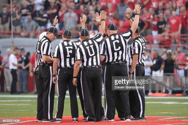 The officials of the contest meet at the center of the field before the game between the Nebraska Cornhuskers and the Arkansas State Red Wolves at...