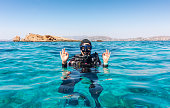 Female scuba diver gives the OK sign in turquoise waters