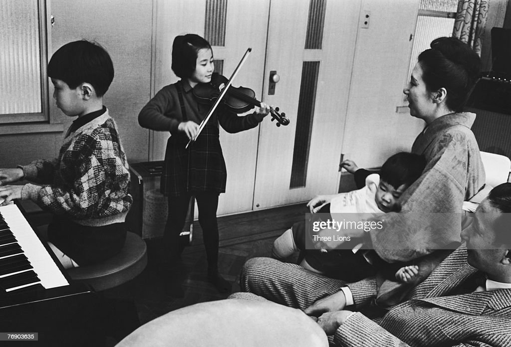 The Okabe family sit down to an evening of music at their home in Nagasaki, circa 1965. Masaya plays the piano and his sister Satomi accompanies him on the violin, while little Kozo squirms on his mother's lap.