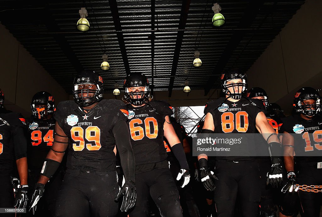 The Oklahoma State Cowboys walk to the field before play against the Purdue Boilermakers during the Heart of Dallas Bowl at Cotton Bowl on January 1, 2013 in Dallas, Texas.
