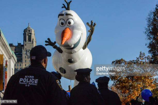 The Olaf from 'Frozen' balloon is led down Central Park West as NYPD officers look on during the annual Macy's Thanksgiving Day parade on November 23...