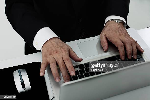 The old age businessman's hand with a PC