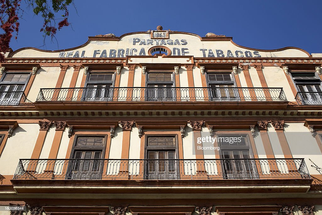 The old architectural exterior of the Partagas cigar factory stands in Havana, Cuba, on Thursday, Jan. 17. 2013. In a country where the average monthly salary is $19, according to Cuba's statistics agency, even buying an airplane ticket will be beyond the reach of most of the island's 11 million residents as President Raul Castro begins easing travel rules on the communist island. Photographer: Andrey Rudakov/Bloomberg via Getty Images