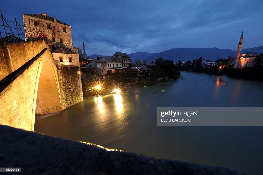 The 'Old Bridge' in the historical core of the Southern-Bosnian town of Mostar, is seen while level of Neretva river has risen for approximately 3 metres in comparison to its normal summertime levels, on April 3, 2013. Water levels have dramaticaly risen countrywide, due to snow-melt and large quantities of rain in the past 7 days. AFP PHOTO ELVIS BARUKCIC