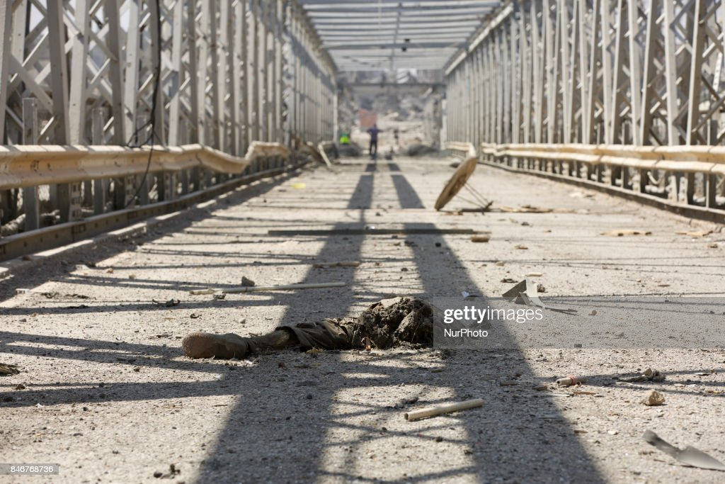 The old city of West Mosul across the Tigris by the old bridge. A dead IS fighter lies on the bridge. Mosul, Iraq, 13 September 2017