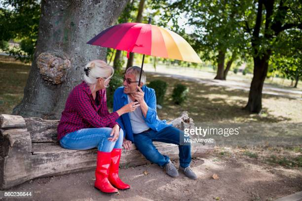 The old couple in the rain with umbrellas