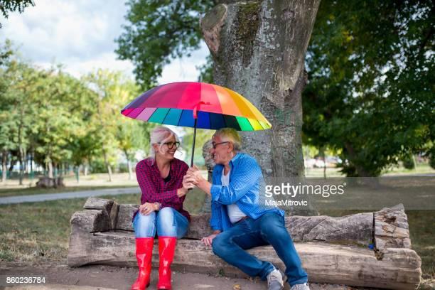 Das alte Paar im Regen mit Regenschirm