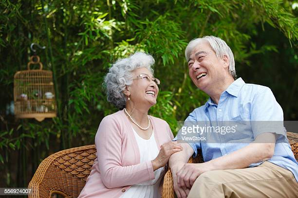 The old couple sitting on a chair in the garden