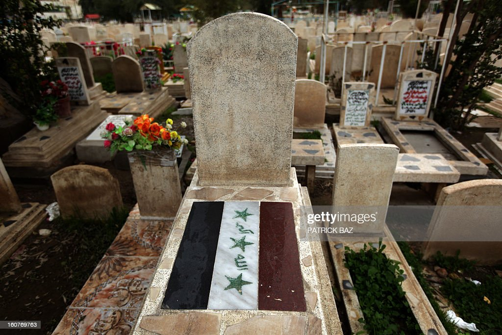 The old Iraqi flag is painted on a tomb of a man killed in 2006 in the Martyrs Cemetery outside the Sunni Abu Hanifa mosque in the Sunni stronghold of Adhamiya on February 05, 2013 in Baghad. The Saddam Hussein-era flag decorates the tombs of Iraqi fighters killed while fighting US troops during the US occupation of the country.