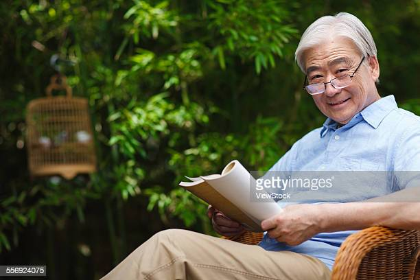 The old man leisure reading in the yard