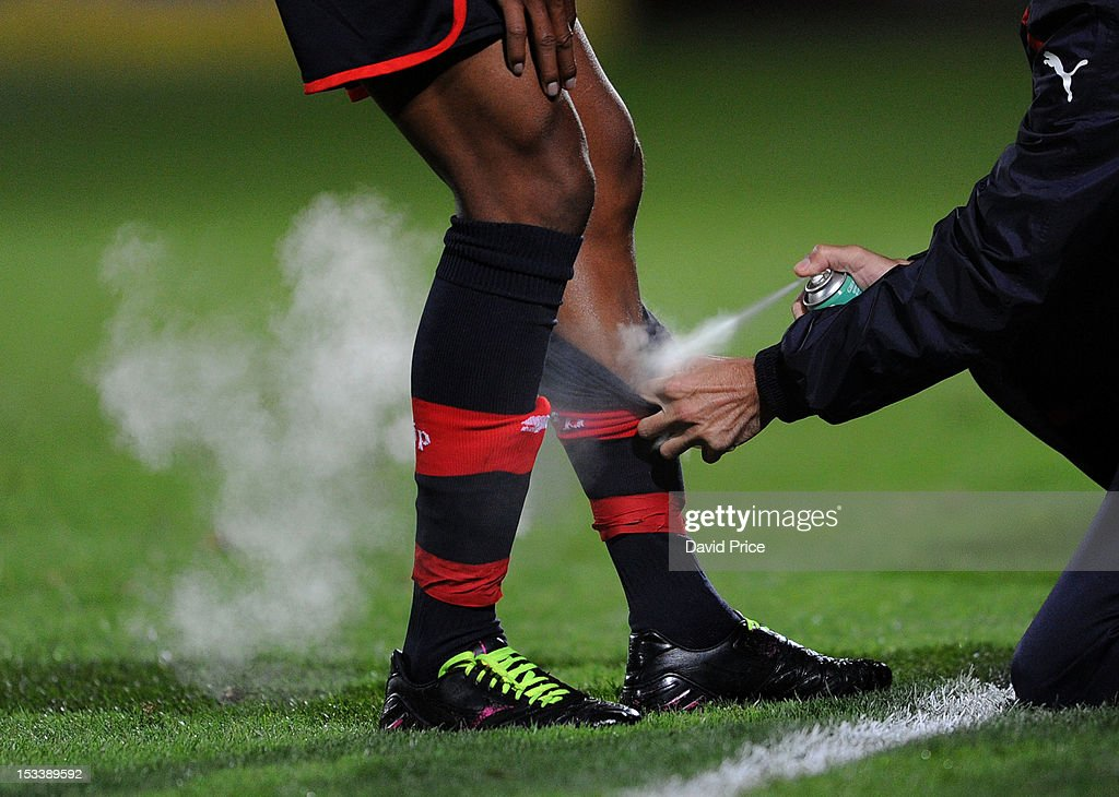 The Olympiacos physio sprays a player's leg during the NextGen Series match between Arsenal U19 and Olympiacos U19 at Underhill Stadium on October 4, 2012 in Barnet, United Kingdom.