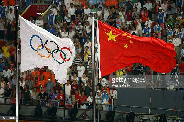 The Olympic flag andd the Chinese national flag fly during the Opening Ceremony for the 2008 Beijing Summer Olympics at the National Stadium on...