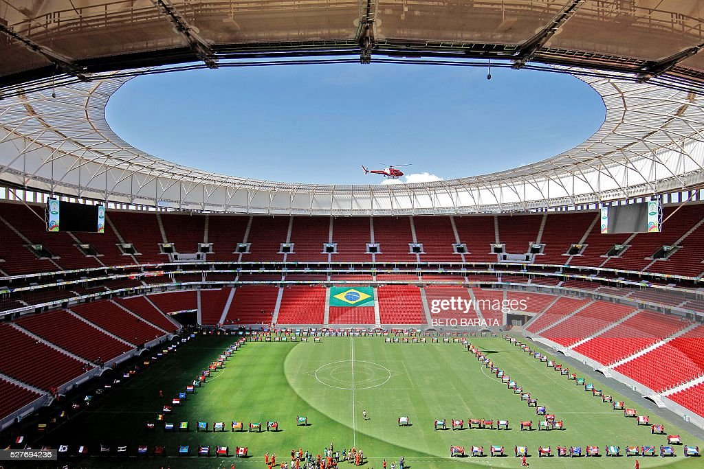 The Olympic flame arrives in helicopter at the Brasilia National Stadium in Brasilia on May 3, 2016. Embattled President Dilma Rousseff greeted the Olympic flame in Brazil on Tuesday, promising not to allow a raging political crisis, which could see her suspended within days, to spoil the Rio Games. The torch will now be carried in a relay by 12,000 people through 329 cities, ending in Rio's Maracana stadium on August 5 for the opening ceremony. / AFP / BETO