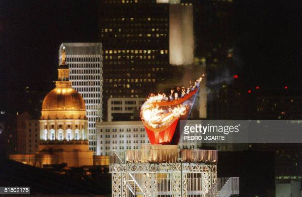 The Olympic flame as seen in front of the skyline of the southern Georgian city of Atlanta early 20 July 1996 at the end of the Centennial Olympic...