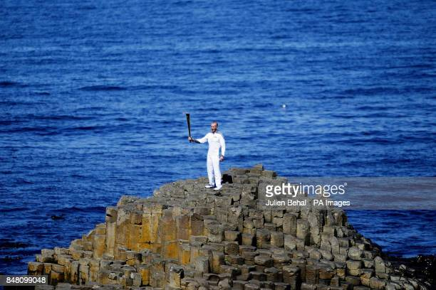 The Olympic Flame is carried onto the famous landmark of the Giant's Causeway outside the village of Bushmills CoAntrim by carrier Peter Jack
