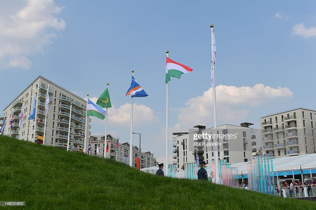 The Olympic Games flag (R), along with those of Hungary (2-R), the Marshall Islands (3-R), Mauritania (4-R) and Uzbekistan (5-R) flutter in the wind during a flag raising ceremony in London on July 25, 2012, two days before the start of the London 2012 Olympic Games.
