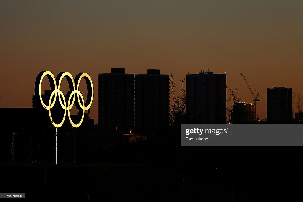 The Olympic rings are illuminated during a sunset, backdropped by apartment blocks near Stratford, inside the Olympic Park before the Revolution 5 at the Velodrome in the Lee Valley Velopark on March 15, 2014 in London, England.