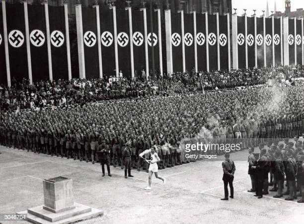 The Olympic torch is carried into the stadium during the opening ceremonies of the XI Olympic Games at the Olympic Stadium in Berlin Germany on...