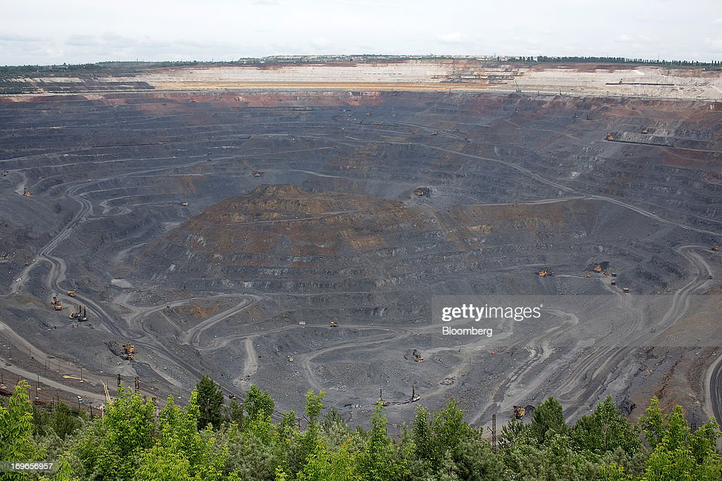 The open pit of Lebedinsky GOK (LGOK) iron ore mining and processing plant, operated by Metalloinvest Holding Co., is seen in Gubkin, Russia, on Tuesday, May 28, 2013. Lebedinsky, Russia's third biggest iron ore mine, is owned 81 percent owned by Russian billionaire Alisher Usmanov, who also owns Mikhailovsky GOK, Russia's second-biggest iron ore mine, and Oskol Electrometallurgical Combine, a steel plant supplied by Lebedinsky. Photographer: Andrey Rudakov/Bloomberg via Getty Images