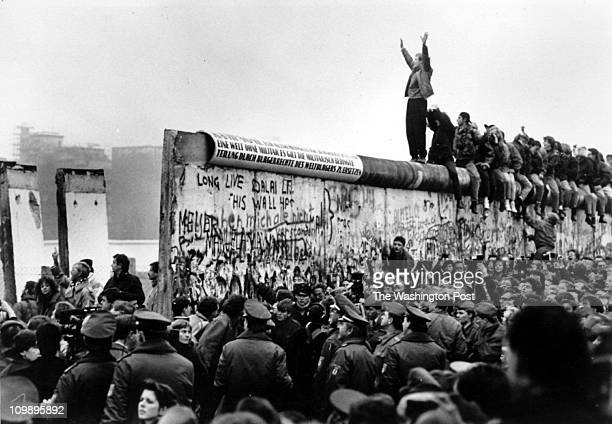 11/12/89 The opening of the Berlin Wall at Potsdamer Platz East Germans pour through the newly opened wall as a West Berliner cheers them on from on...