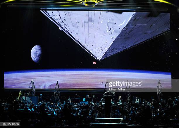 The opening space battle scene from 'Star Wars Episode IV A New Hope' is shown on screen while musicians perform during 'Star Wars In Concert' at the...