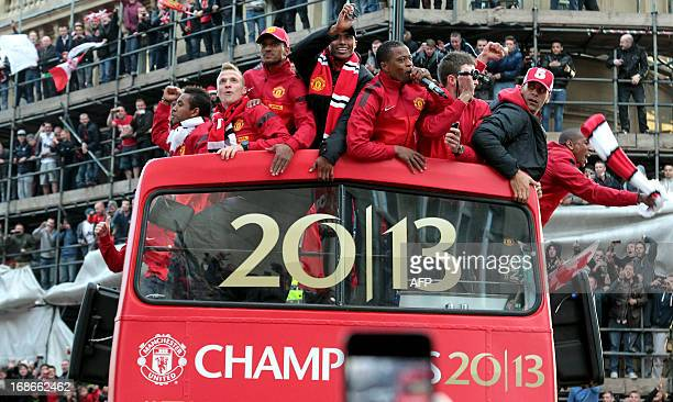 The opentop bus carrying Manchester United players passes along Deansgate in the city centre of Manchester north west England on May 13 2013 during...
