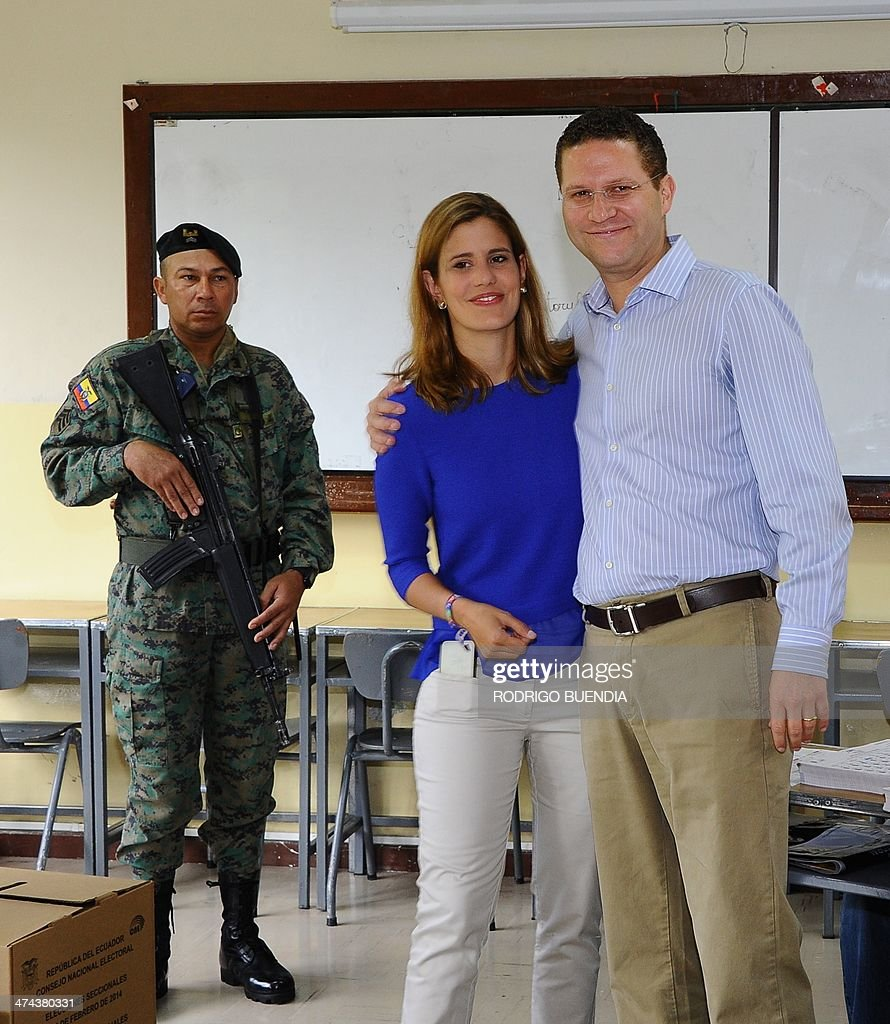 The opposition candidate for Quito's Mayor's Office, Mauricio Rodas, accompanied by his wife Maria Fernanda Pacheco, poses after casting his vote at a polling station in northern Quito, as Ecuador holds municipal elections on February 23, 2014.