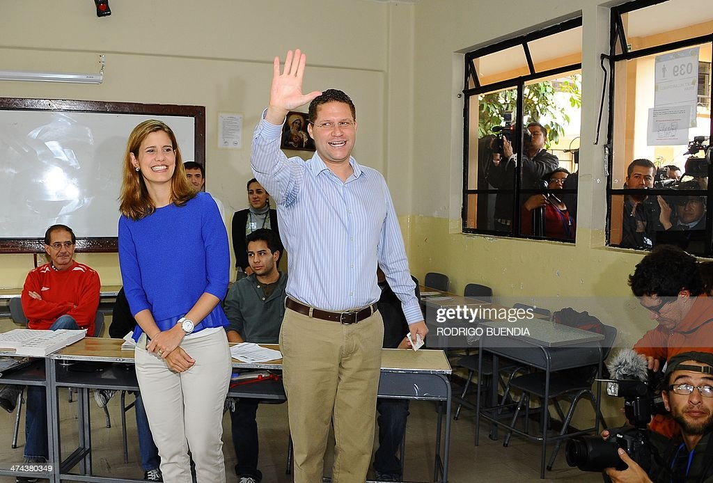 The opposition candidate for Quito's Mayor's Office, Mauricio Rodas, accompanied by his wife Maria Fernanda Pacheco, waves after casting his vote at a polling station in northern Quito, as Ecuador holds municipal elections on February 23, 2014.