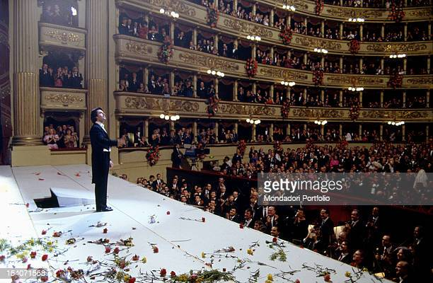 The orchestra director at the end of his performance at the Scala Theatre receives the applause and the launch of flowers from the audience and the...