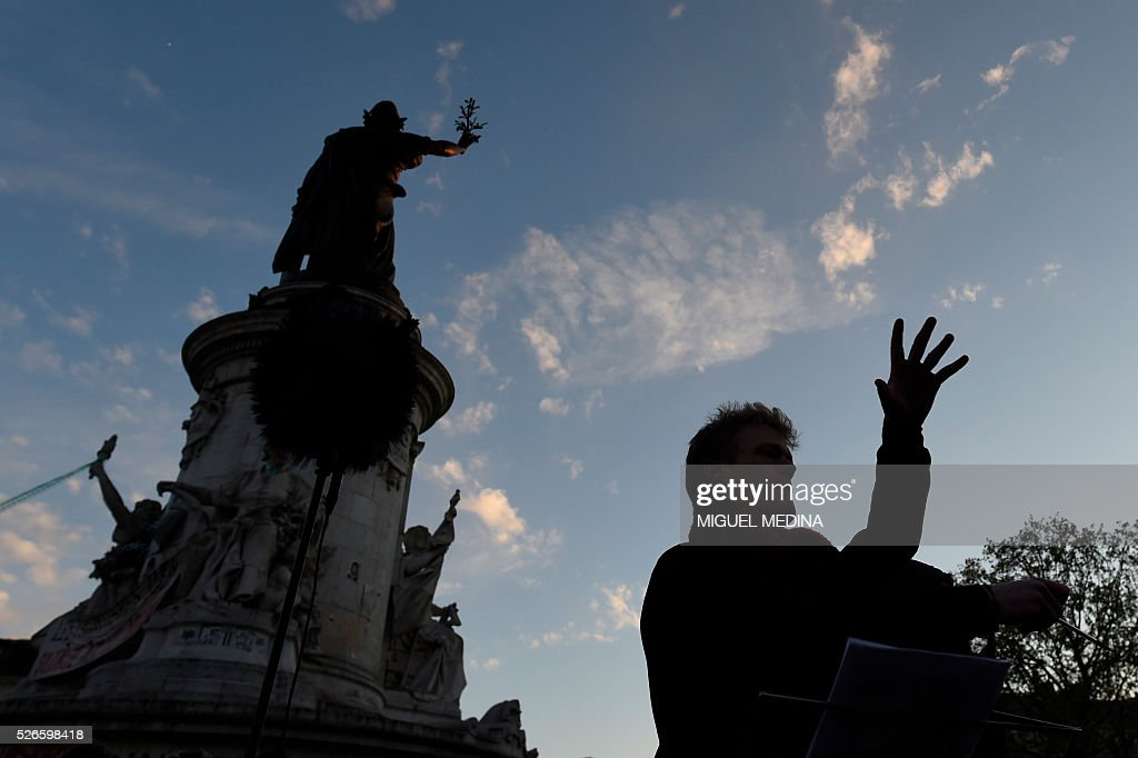 The orchestra of classical music 'Standing Musicians' perform during the 'Nuit Debout' (Up All Night) movement against the French government's proposed labour reforms at the Place de la Republique in Paris on April 30, 2016. / AFP / MIGUEL