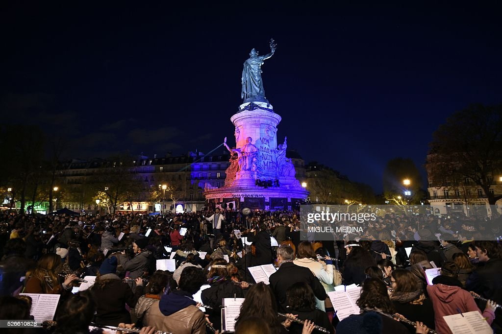 The orchestra of classical music 'Standing Musicians' performs during the 'Nuit Debout' (Up All Night) movement against the French government's proposed labour reforms at the Place de la Republique in Paris on April 30, 2016. / AFP / MIGUEL