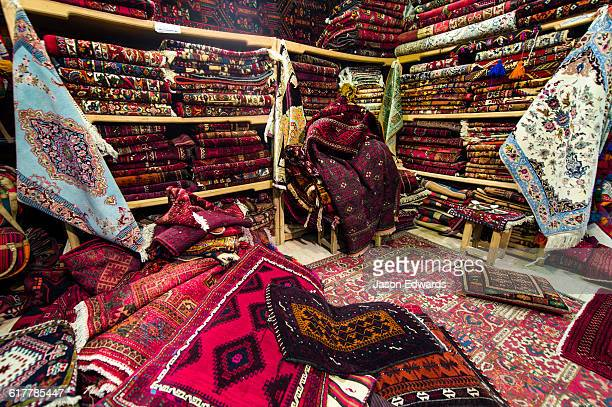 The ordered chaos of a Persian carpet shop in an ancient bazaar.