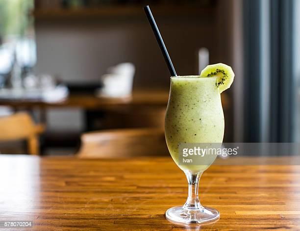The Organic Fresh Kiwi Juice on Wood Table with Sunlight