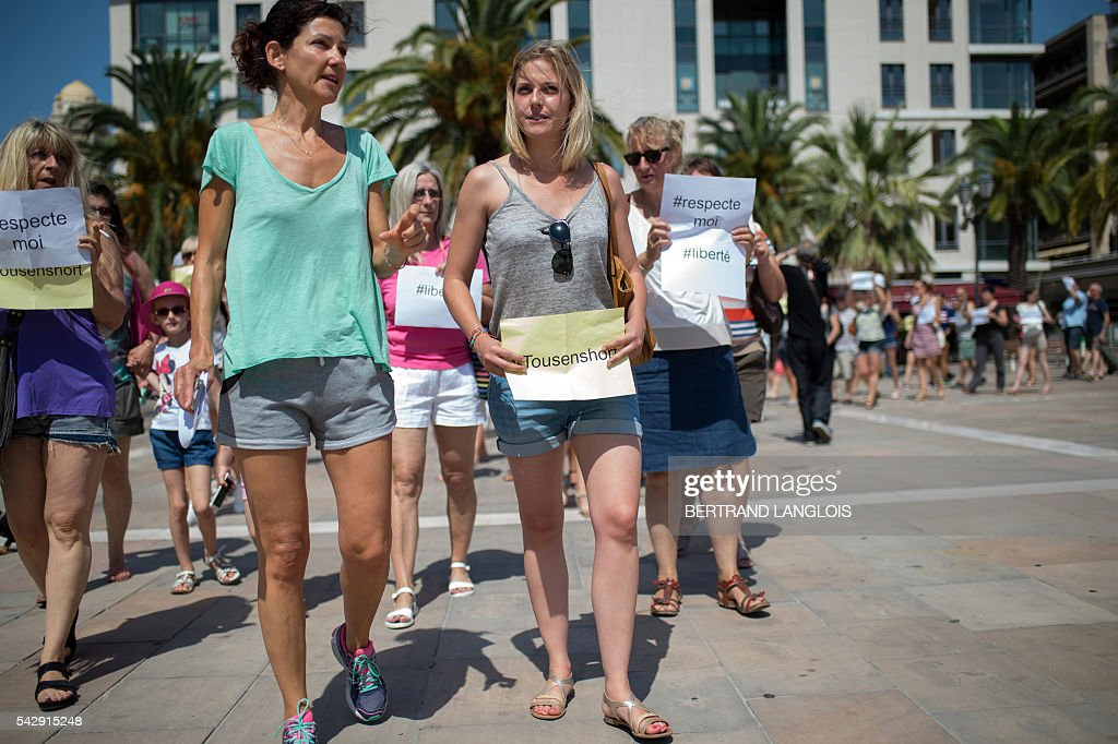 The organiser of the 'Marche des Shorts' (The March of the Shorts) Cecile Muschotti (C) holds a sign reading 'All in shorts' as she attends a rally to show support to a young woman who was attacked in a bus because she wearing shorts, in Toulon, southeastern France, on June 25, 2016. / AFP / BERTRAND