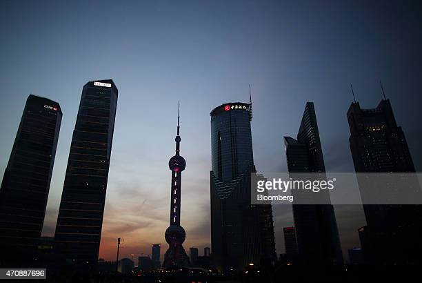 The Oriental Pearl Radio TV Tower third from left and other commercial buildings stand at dusk in the Lujiazui district of Shanghai China on Thursday...