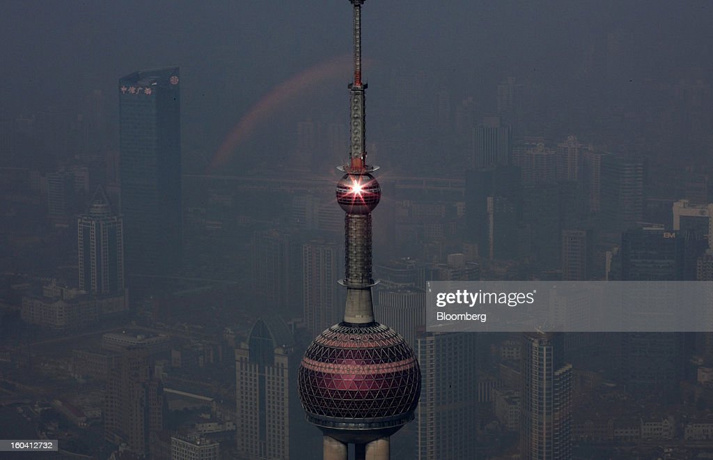 The Oriental Pearl Tower is viewed through a colored glass window from the Shanghai World Financial Center as sun reflects off it in the Pudong area of Shanghai, China, on Wednesday, Jan. 30, 2013. China's economic growth accelerated for the first time in two years as government efforts to revive demand drove a rebound in industrial output, retail sales and the housing market. Photographer: Tomohiro Ohsumi/Bloomberg via Getty Images