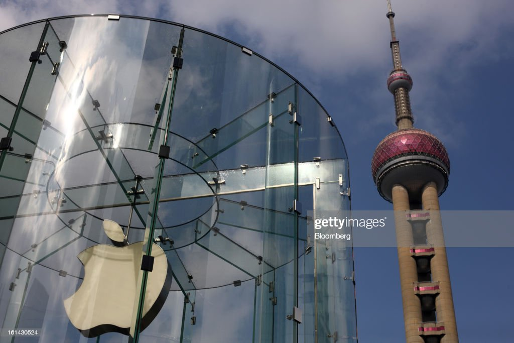 The Oriental Pearl Tower, right, stands behind the Apple Inc. logo displayed at one of the company's stores in the Pudong area of Shanghai, China, on Saturday, Feb. 9, 2013. China's services industries grew at the fastest pace since August as gains in retailing and construction aid government efforts to drive a recovery in the world's second-biggest economy. Photographer: Tomohiro Ohsumi/Bloomberg via Getty Images