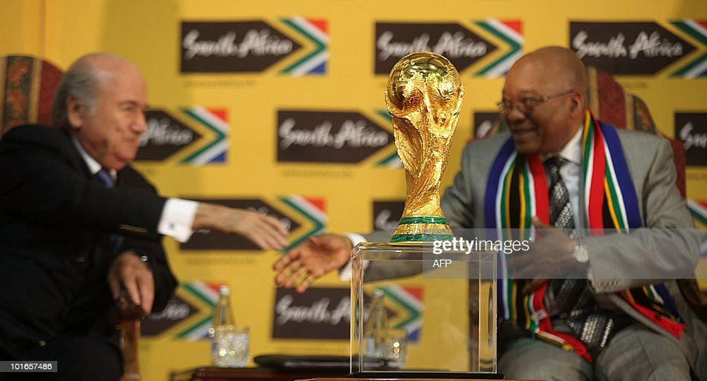 The original FIFA World Cup trophy (C) is pictured as South African President Jacob Zuma (R) reaches to shake hands with FIFA president Sepp Blatter (L) during a press briefing at the presidential guest house in Pretoria on June 6, 2010 five days before the kick off of the World Cup football tournament. The 2010 World Cup will take place in South Africa from June 11 to July 11, the first time on African soil for the biggest and most prestigious competition in sport.