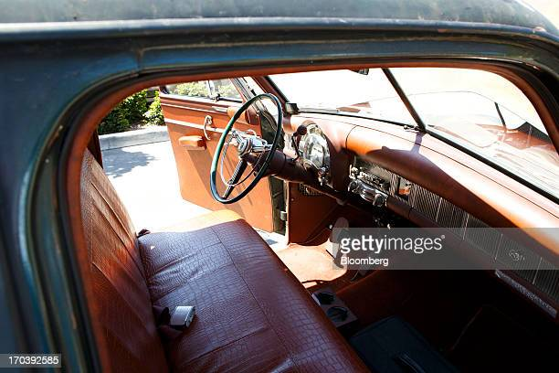 The original steering wheel and wood flooring of a 1952 Chrysler Group LLC Town Country Wagon with the front end of a DeSoto grafted on is displayed...