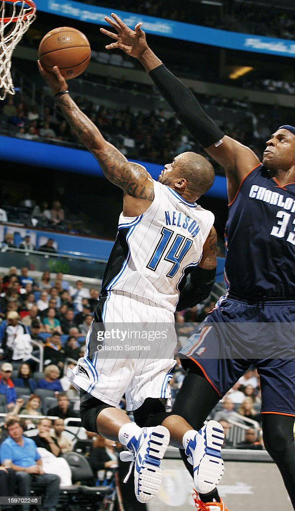 The Orlando Magic's Jameer Nelson (14) scores under the Charlotte Bobcats' Brendan Haywood at the Amway Center in Orlando, Florida, on Friday, January 18, 2013. Charlotte won, 106-100.