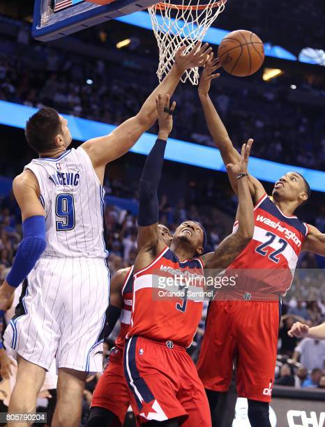 The Orlando Magic's Nikola Vucevic and the Washington Wizards' Bradley Beal and Otto Porter battle for the ball late in the fourth quarter at the...