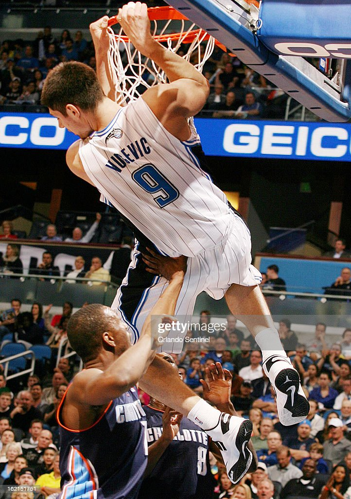 The Orlando Magic's Nikola Vucevic (9) hangs from the rim after a slam dunk over the Charlotte Bobcats' Ramon Sessions (7) and Ben Gordon (8) at the Amway Center in Orlando, Florida, on Tuesday, February 19, 2013.
